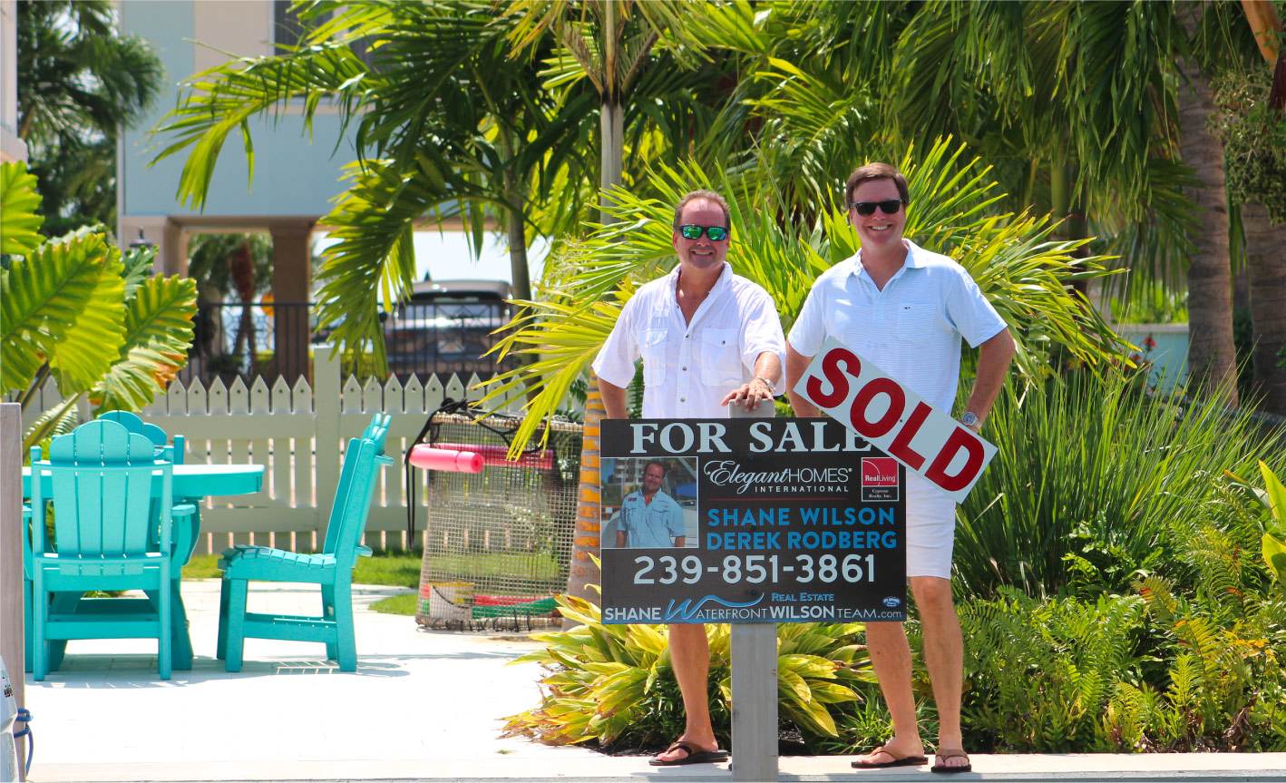 Shane WIlson and Derek Rodberg with sold property sign in the Florida Keys